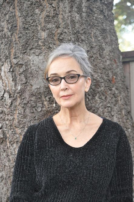 Sarah Arnold, a white woman with grey hair in a bun, leans against a tree, and smiles softly at the camera. SHe wears a knit black sweater, and a silver necklace and earrings