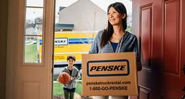 Woman walking through the front door carrying a Penske box