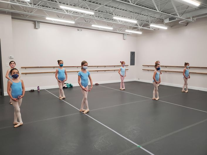 Eight young girls in light blue leotards and masks stand in fifth position in a dance studio.