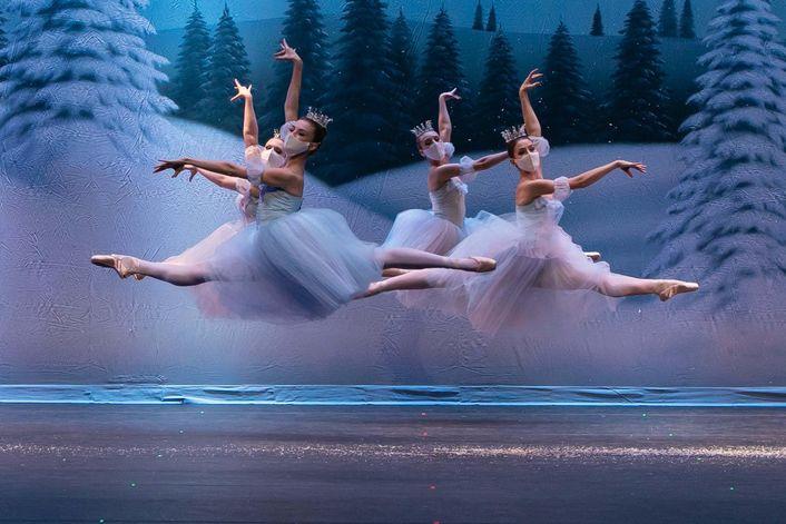 Four teenage girls perform the snow scene from the Nutcracker, leaping in the air wearing blue costumes, crowns and masks