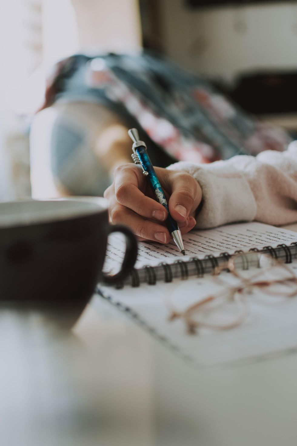 Person's hand writing with a pen onto a notebook with a mug in the foreground.
