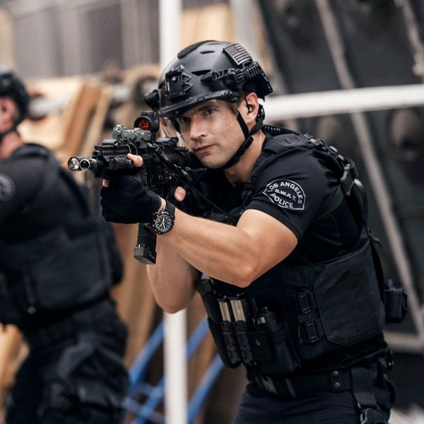A SWAT team membemr wears a helmet with the visor down as he points a gun during a tactical advance.