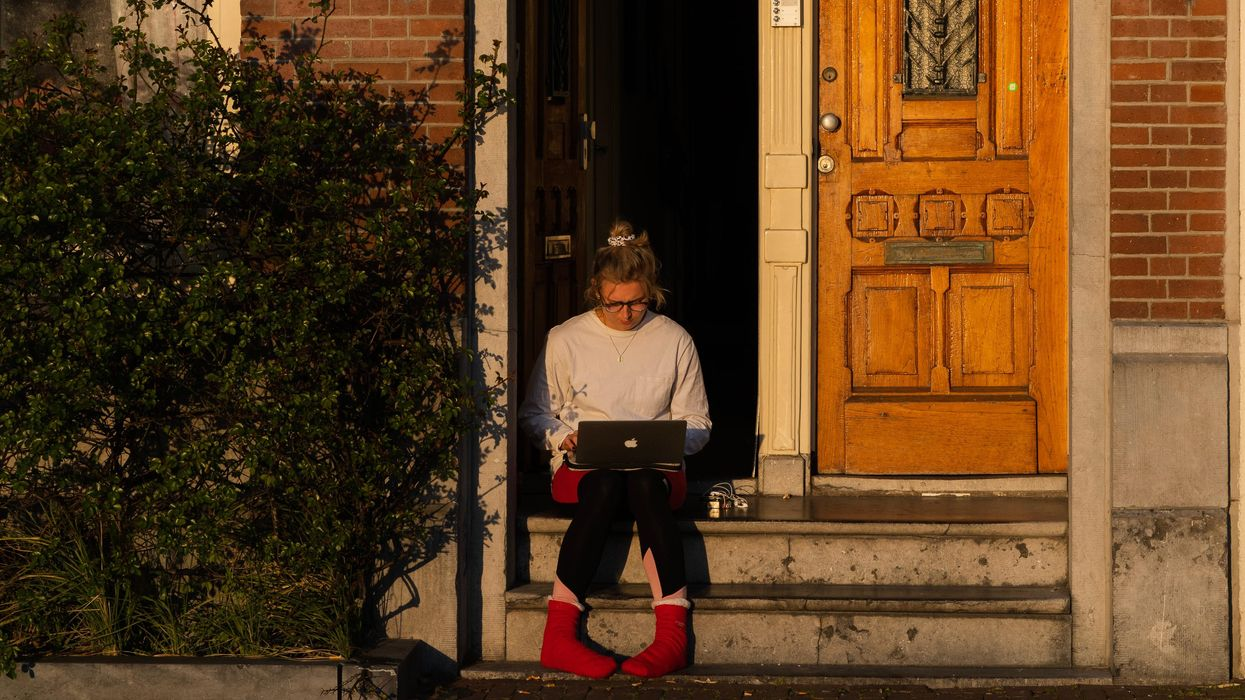 A student sitting on her front step working on a laptop.