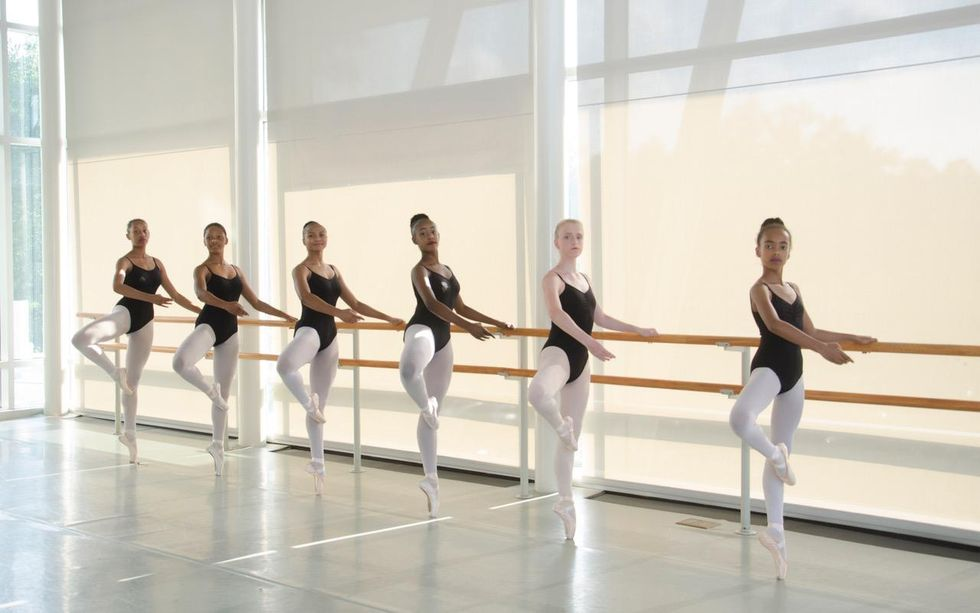 A group of six teenage female ballet students balance at the barre on their left leg in retir\u00e9 on pointe. They wear matching black camisoles, pink tights and pink pointe shoes and look towards the camera; behind them are a large set of floor to ceiling windows covered with large shades.