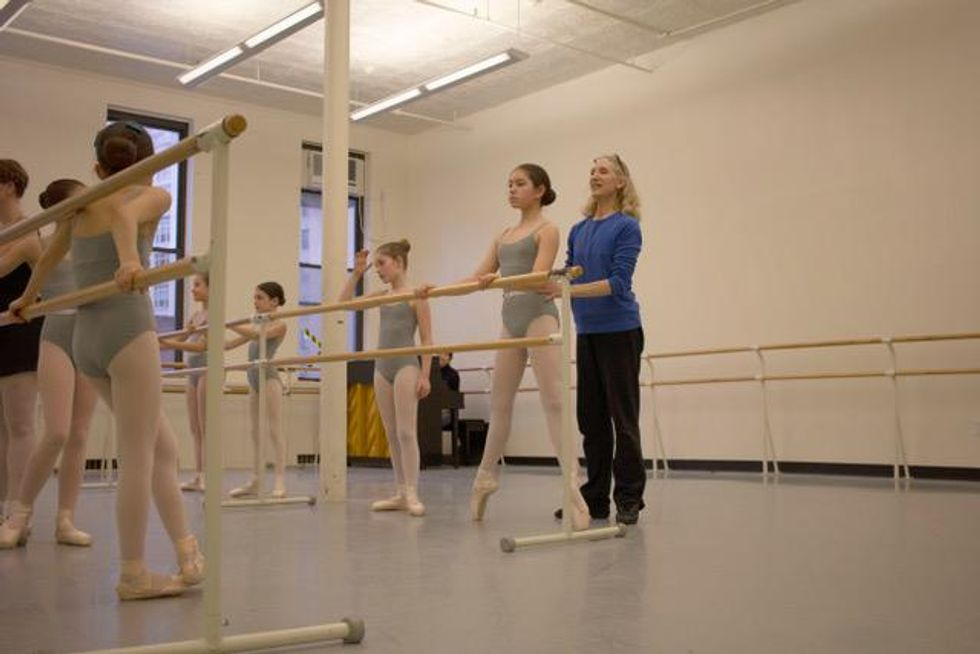 Ballet teacher Gretchen Gunther stands behind a young student facing the barre who is balancing in second position on pointe. Gunther, in a blue shirt and black sweatpants, holds onto her waist as the girl's classmates, all wearing gray leotards, pink tights and pink pointe shoes, look on.