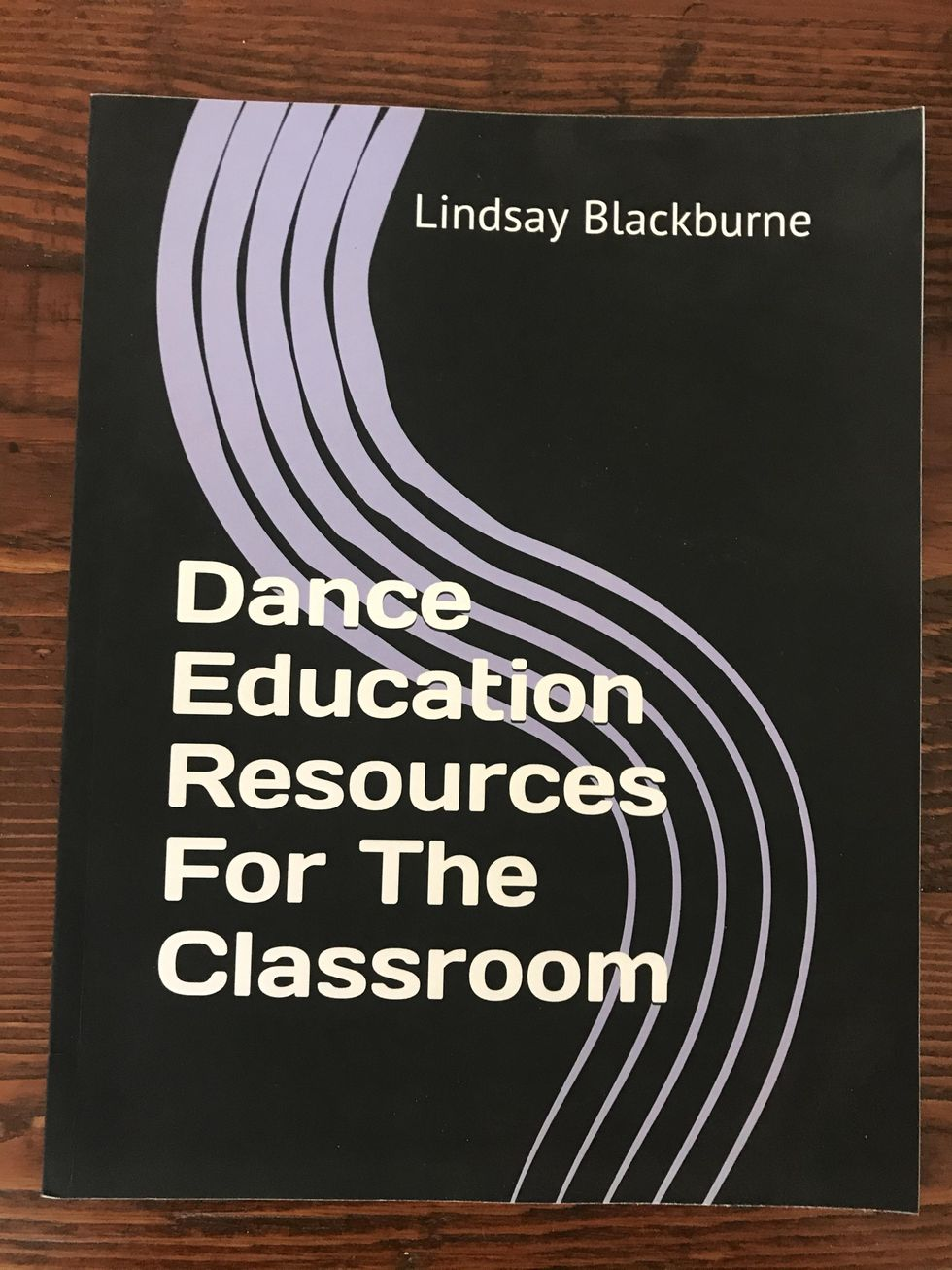 Dance Education Resources for the Classroom lays flat on a wooden table. It is a black paperback book with white text and light purple squiggly lines