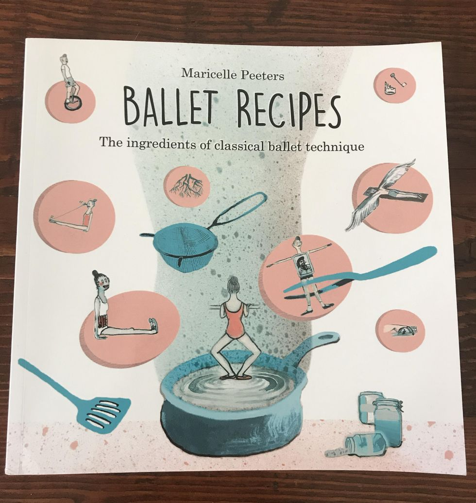 Ballet Recipes lays flat on a wooden table. It is a white paperback book with an illustrated drawing featuring both cooking and ballet images, like a dancer doing a plie at barre in a pot of water