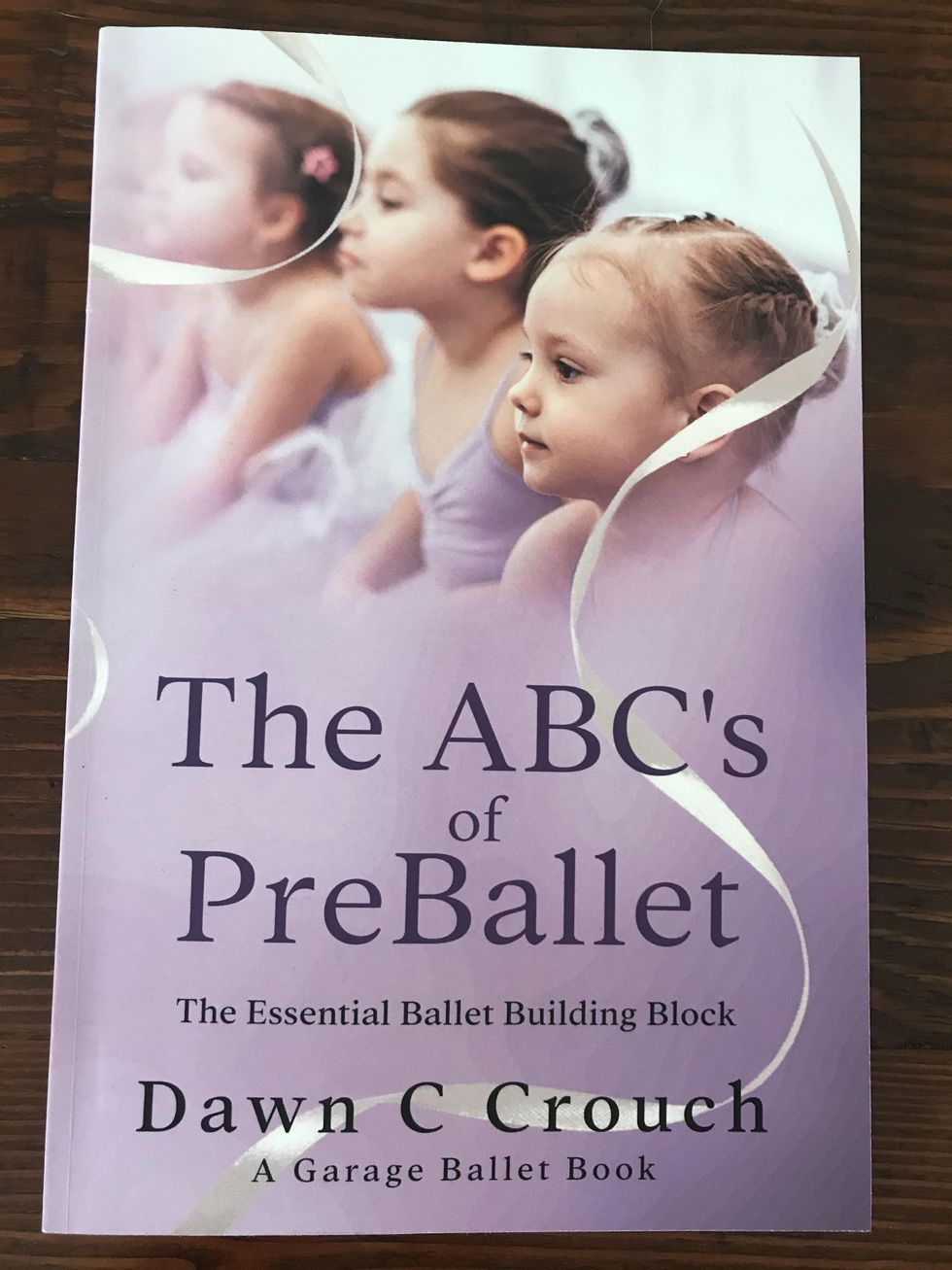 The ABCs of preballet lays flat on a wooden table. It is a purple paperback book, with an image of 3 young girls wearing purple leotards and tutus