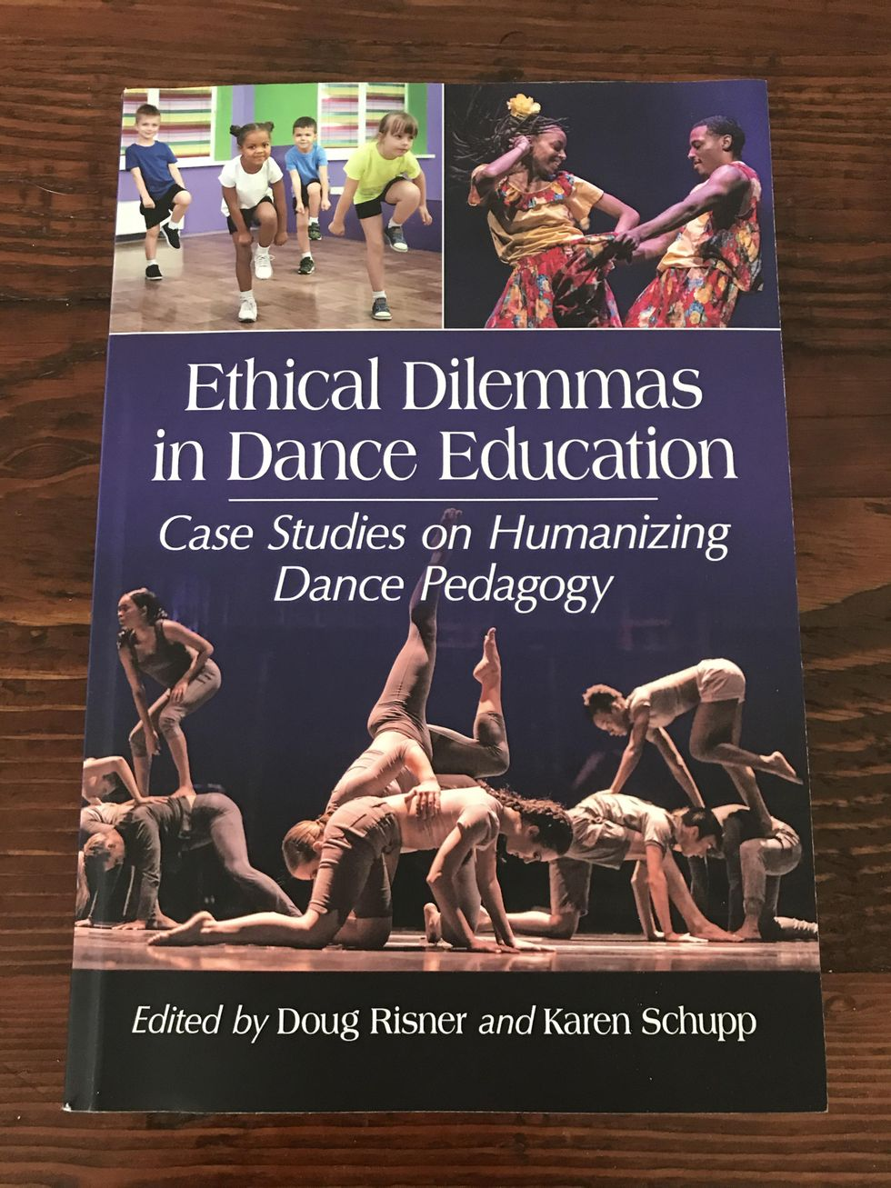 Ethical Dilemmas in Dance Education lays flat on a wooden table. It has three images of dance of different styles, and large white text