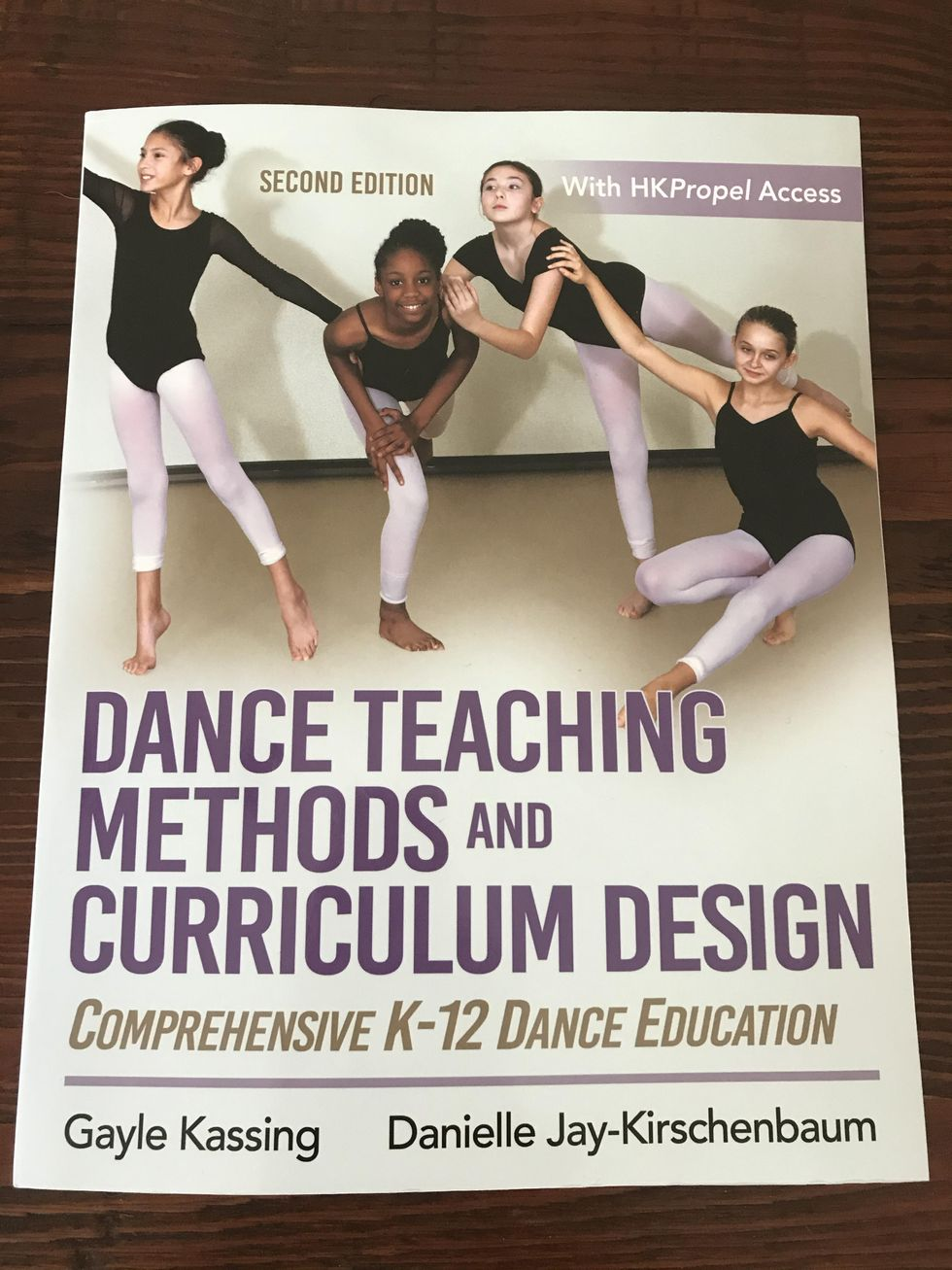 Dance Teaching Methods and Curriculum Design lays flat on a wooden table. It is a large book with large purple print, and an image of four middle school-aged girls in leotards and tights posing