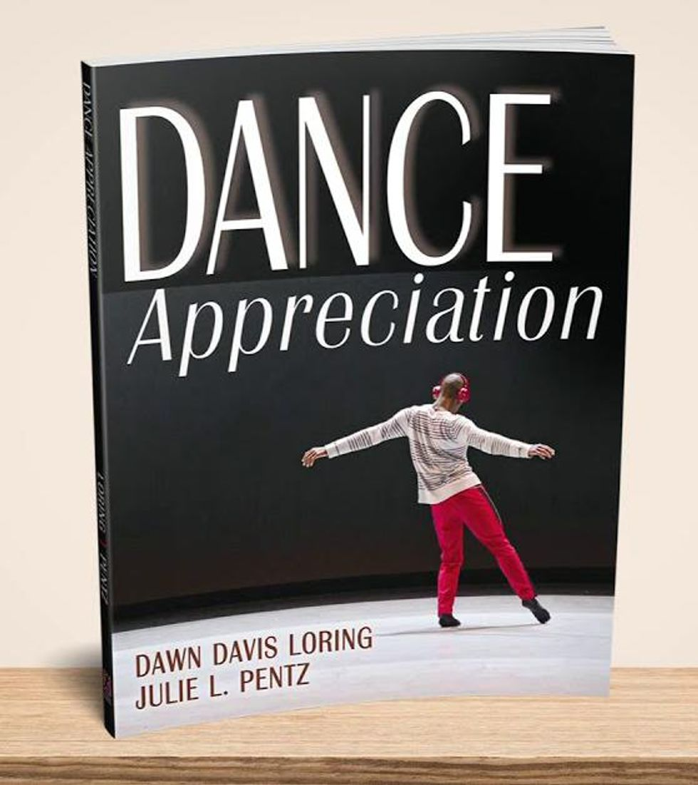Dance Appreciation stands up on a wooden table, against a beige wall. It is a black book with large white text, and features an image of a man dancing with his back to the camera, wearing red headphones