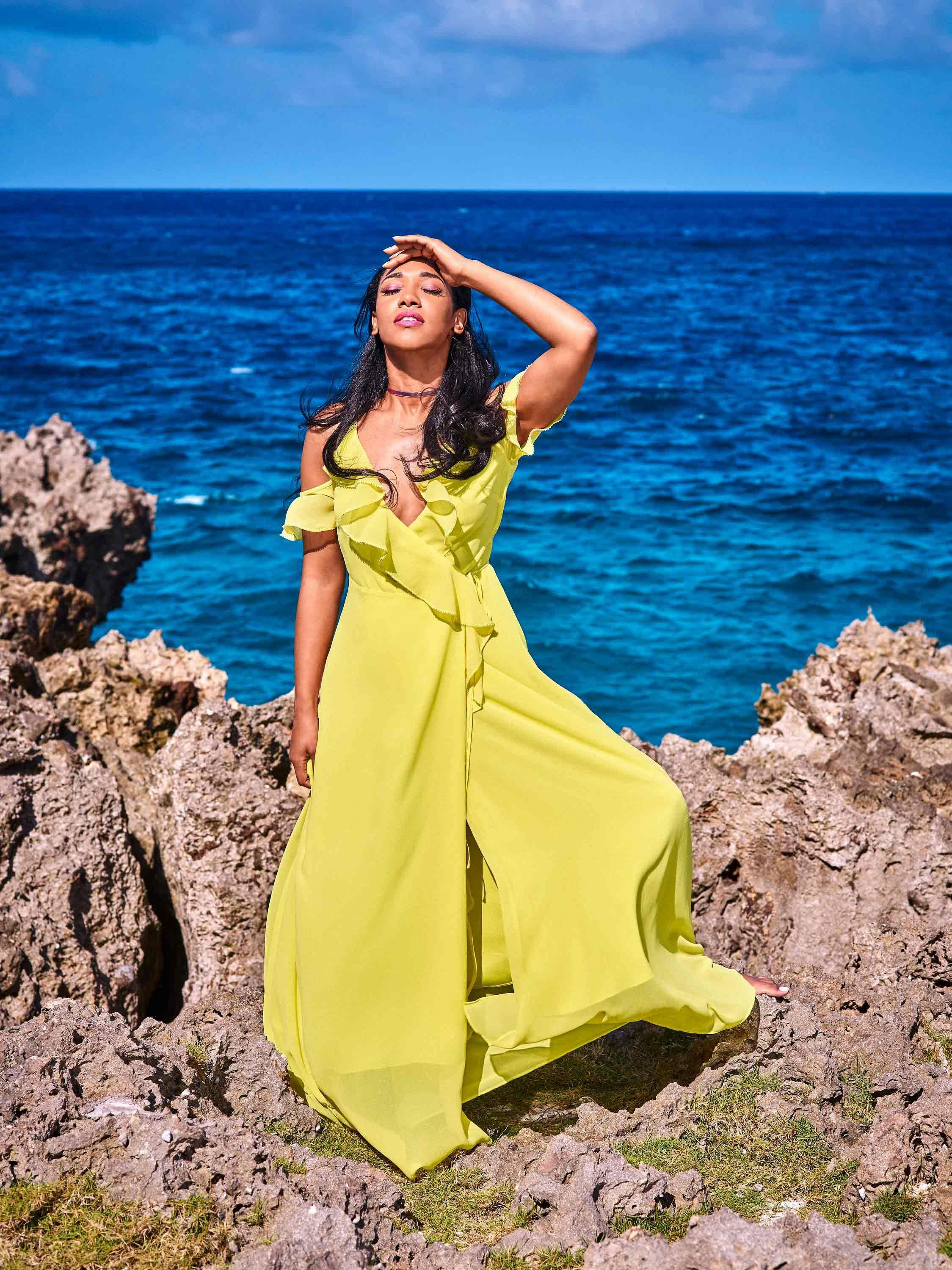 Candice Patton in a neon yellow ruffled dress at the edge of the ocean