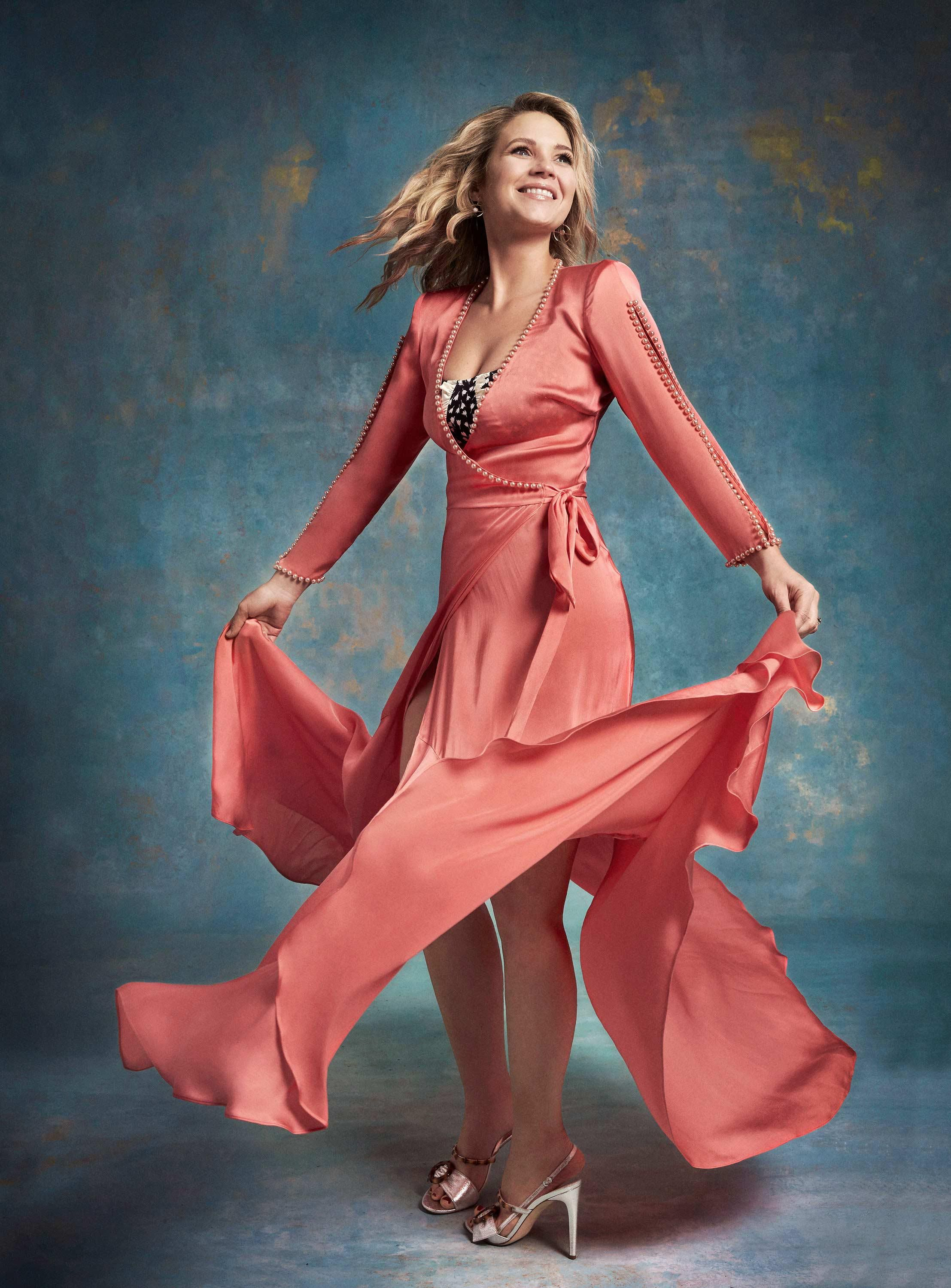 \u200bVanessa Ray models a peach wrap dress with pearls trimming the sleeves