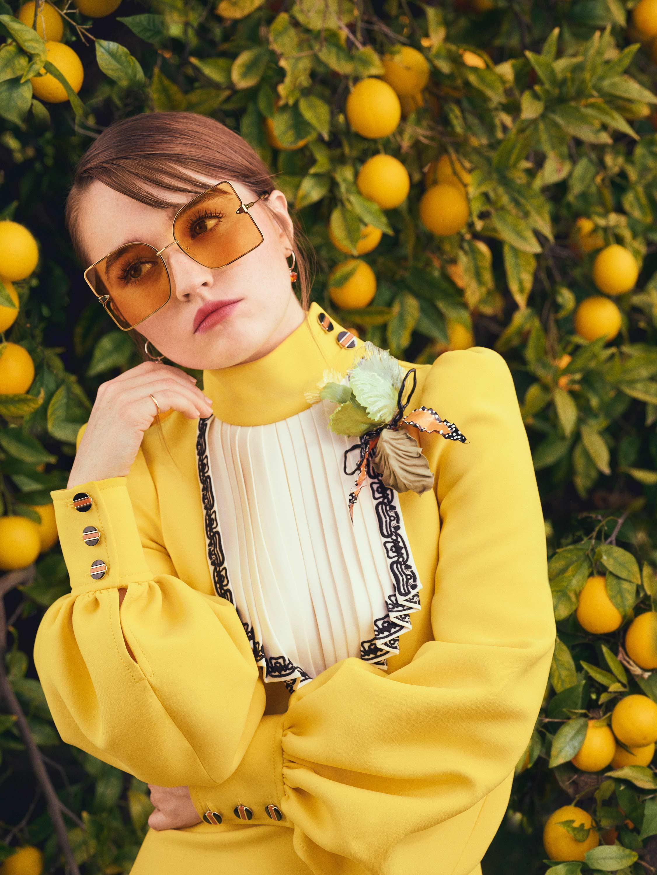 Kaitlyn Dever sports a bright yellow dress with a high collar and a pleated white bib front