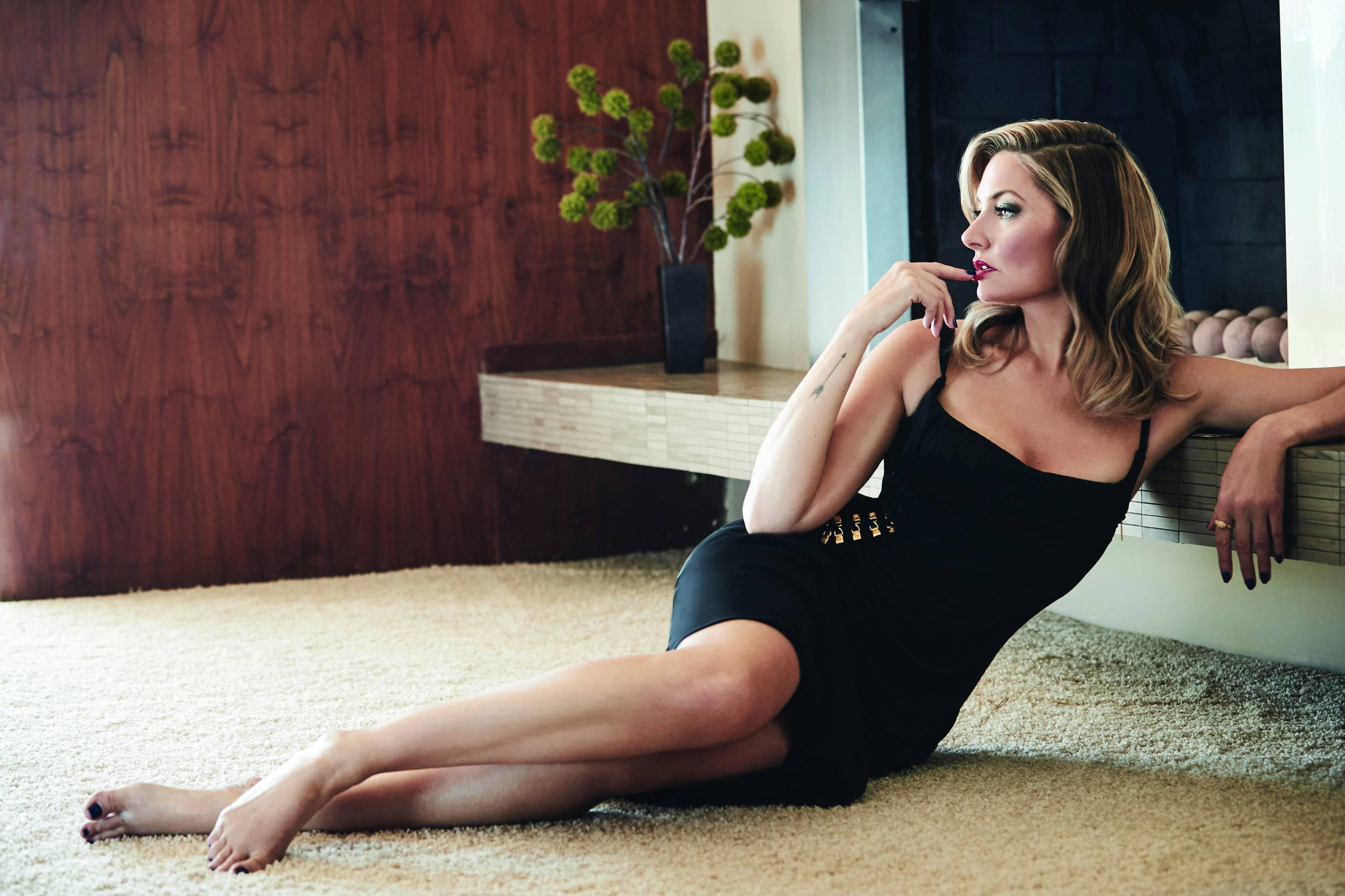 M\u00e4dchen Amick in a black mini dress and matching black toenail polish on her bare feet