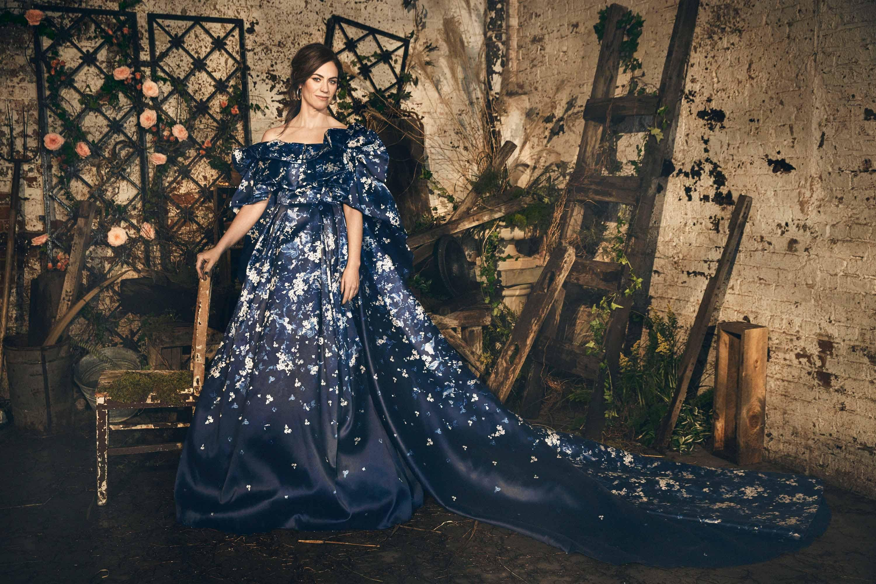 Maggie Siff in a dark blue floral gown with a flowing train