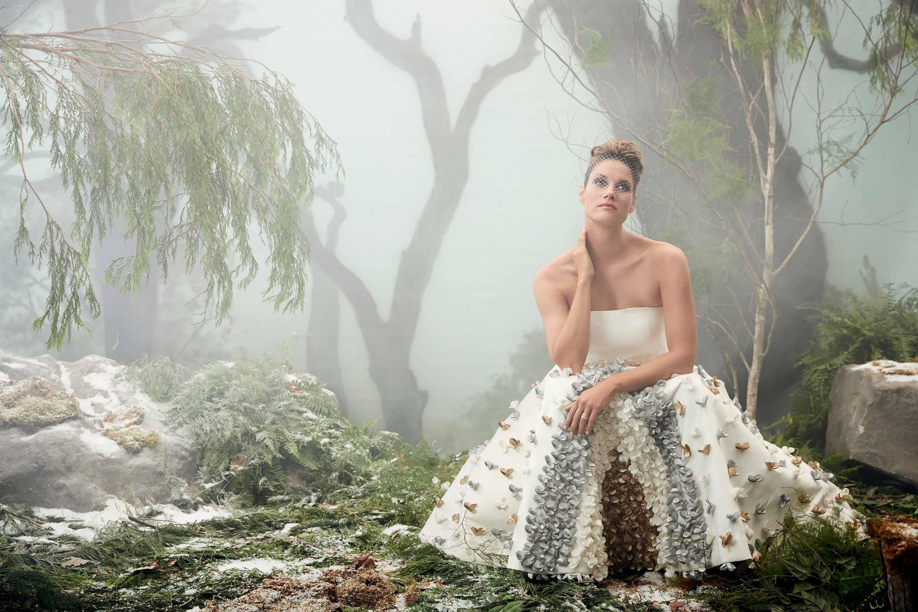 Missy Peregrym poses in a forest setting wearing a strapless white gown with flowers