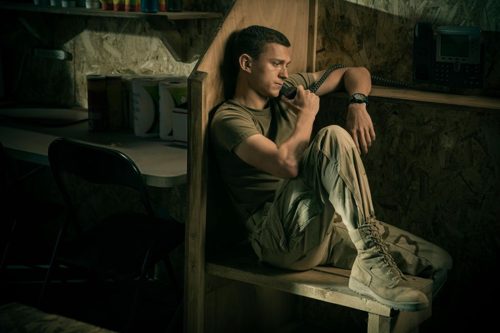"Tom Holland as ""Cherry"" sits near a phone booth as he calls Emily (Ciara Bravo) while stationed in Iraq with the United States Army. He wears a tan shirt, army camoflauge pants and high-lace boots."