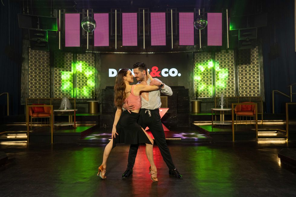Val Chmerkovskiy and Jenna Johnson, both young and white, dance together\u2014she is on her toes and has her arm wrapped around him, he has his arm around her back.