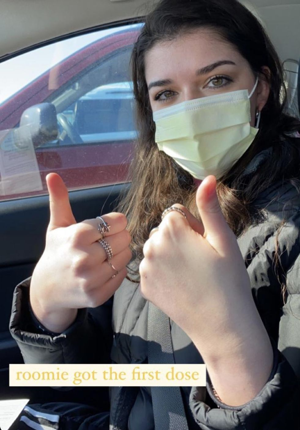 College student with mask on in car.