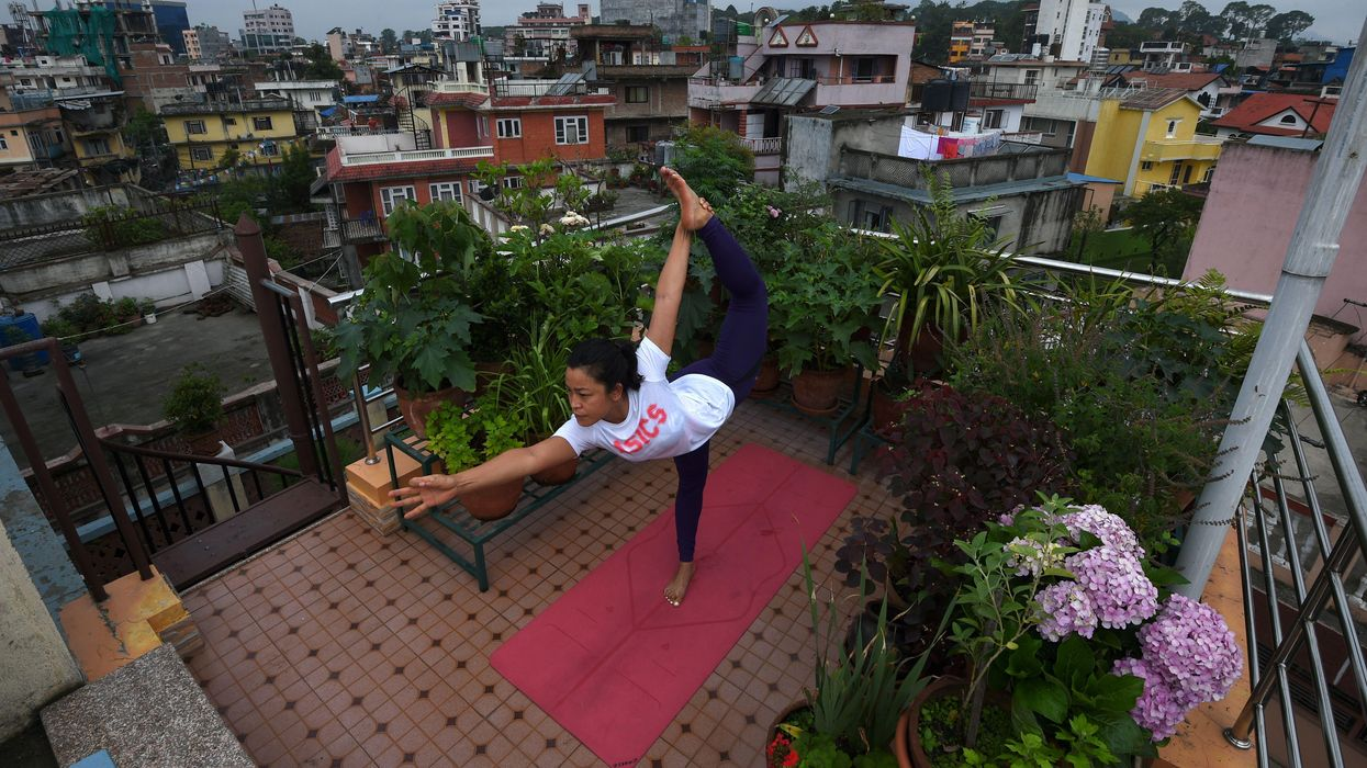 A woman doing yoga on her rooftop terrace in Nepal.