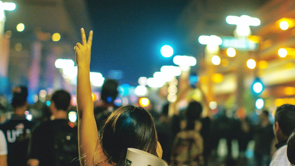 A woman gives the peace sign at a protest.