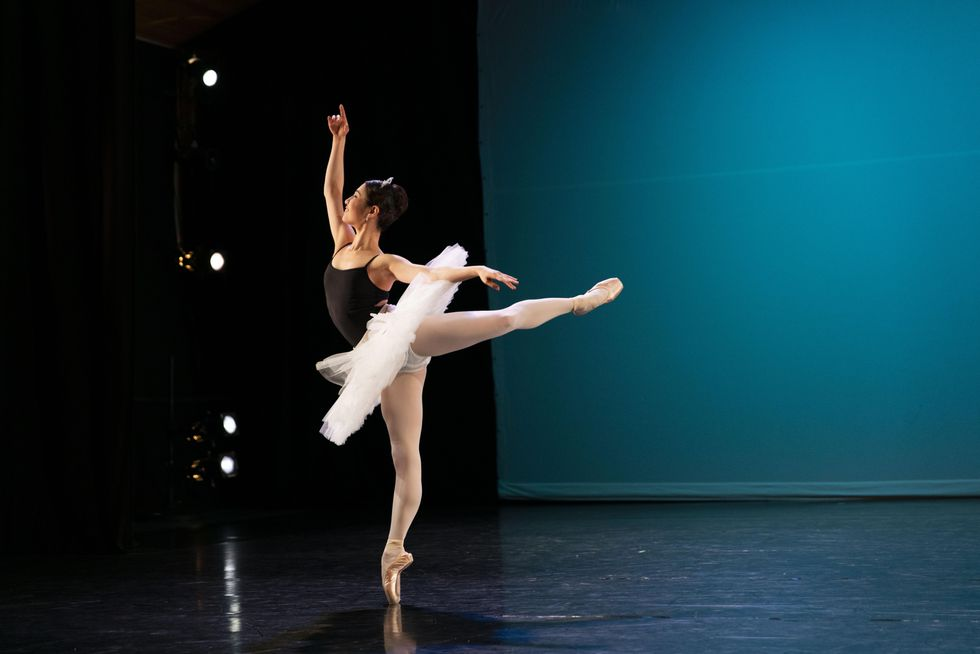Kotomi Yamada, a young Asian ballet dancer, performs a piquu00e9 attitude on pointe on her right leg and looks up toward her raised right arm. She wears a black camisole leotard and white practice tutu and dances on a black box stage in front of a blue backdrop.