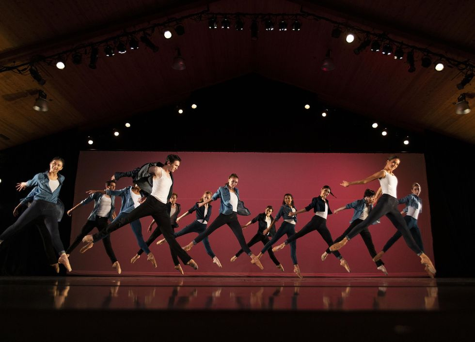 A large group of male and female dancers in black leggings, white T-shits and jean jackets do a sissone with their left legs in front and their arms thrown back. They jump in front of a red backdrop, cocking their heads towards the audience with big smiles.