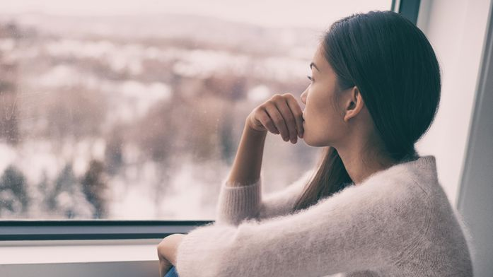woman sitting inside looking outside concept of mental health depression anxiety sadness COVID-19