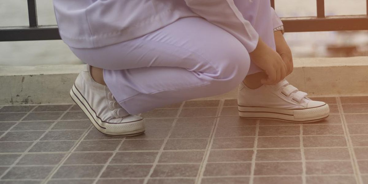 A nurse wearing scrubs bends down to adjust velcro shoes