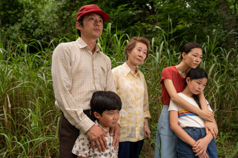 """(Left to right) Steven Yeun, Alan S. Kim, Yuh-Jung Youn, Yeri Han and Noel Cho in """"Minari."""" The family stands in the foreground of some tall bright green grass."""