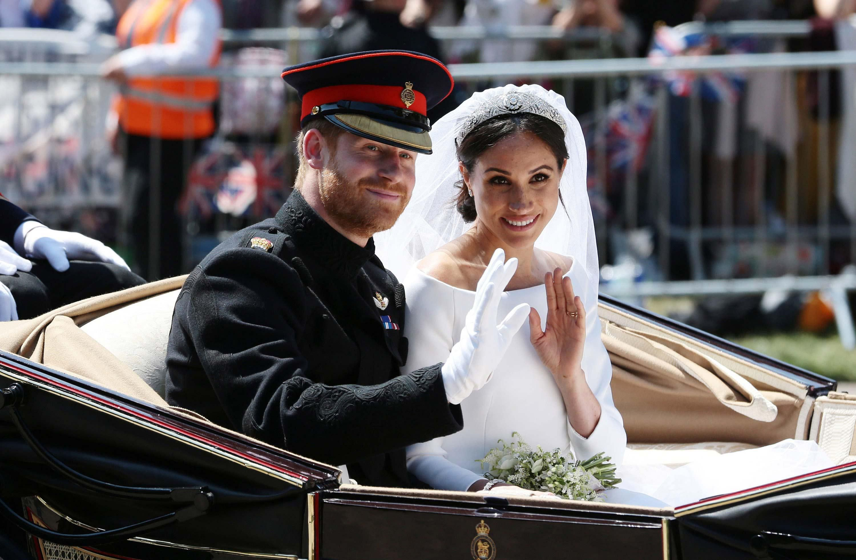 \u200bHarry and Meghan pose for a photo in an open-top carriage at their wedding