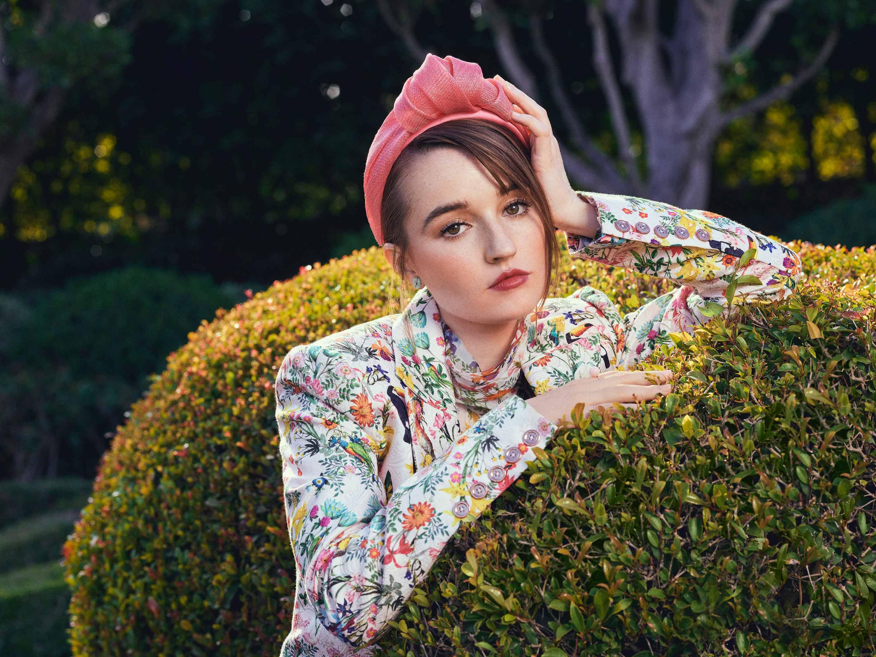 Kaitlyn Dever wears a floral jacket during a garden photo shoot