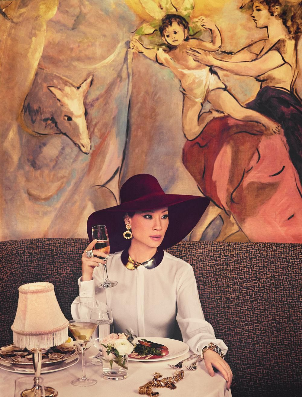 Lucy Liu poses in a restaurant booth in a dramatic burgundy hat