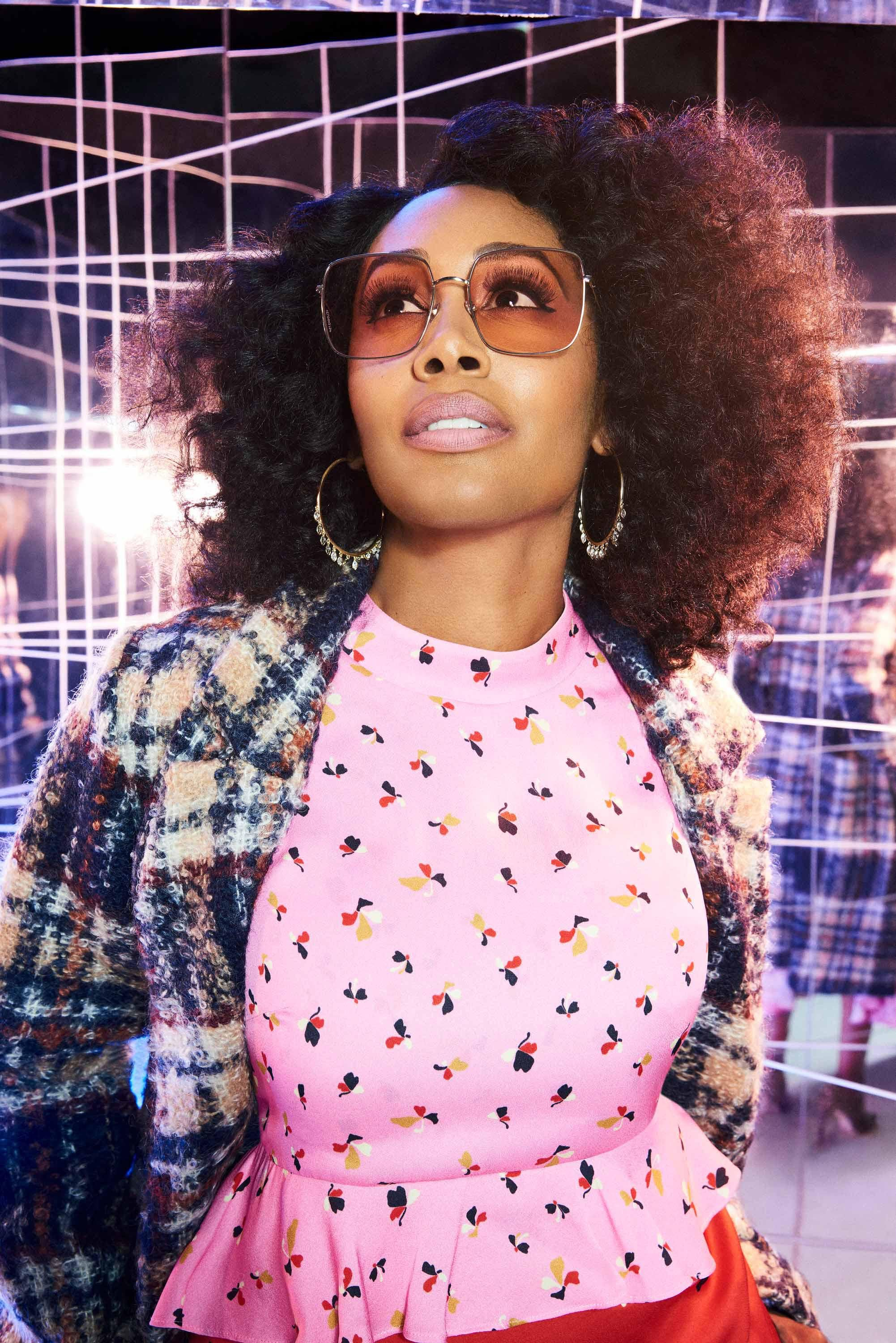 Simone Missick models oversize sunglasses and hoop earrings
