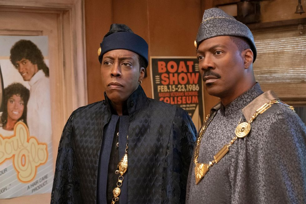 Semmi (left, played by Arsenio Hall) and Prince Akeem (Eddie Murphy) stand side by side in a barbershop in Queens, New York. Both men are wearing regal coats, clothes and giant gold royal necklaces. Arsenio is wearing a black chevron coat over navy clothing while Eddie wears a grey coat. Both wear hats that match their respective outfits.