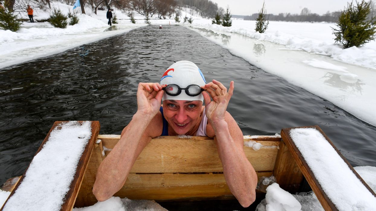 A woman looking up from her swim in icy waters.