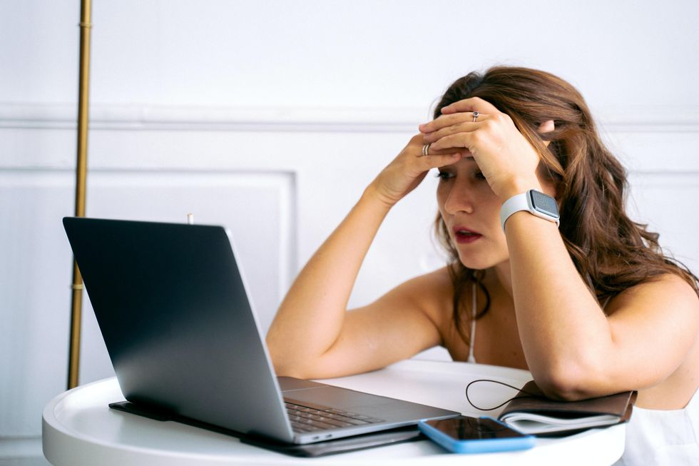 Woman in White Tank Top Using Macbook