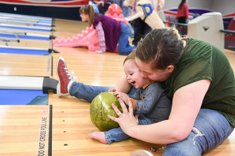 A lady and a child are sitting on a floor in a bowling alley they are holding a green bowling ball