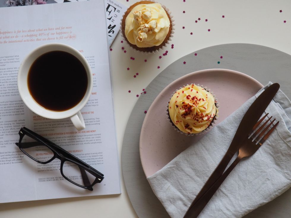 Two cupcakes with a coffee mug, plates, and glasses in the background.