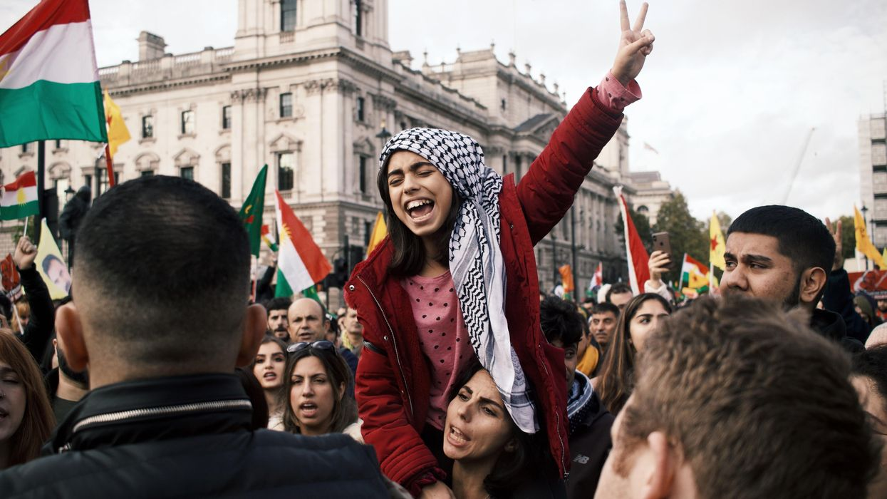A girl gives the peace sign at a protest in London while sitting on a woman's shoulders.