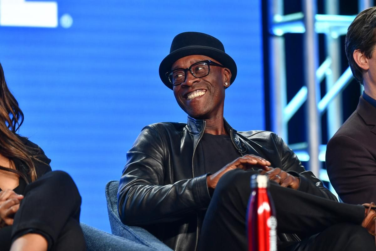 Don Cheadle wearing a hat and smiling during a press tour