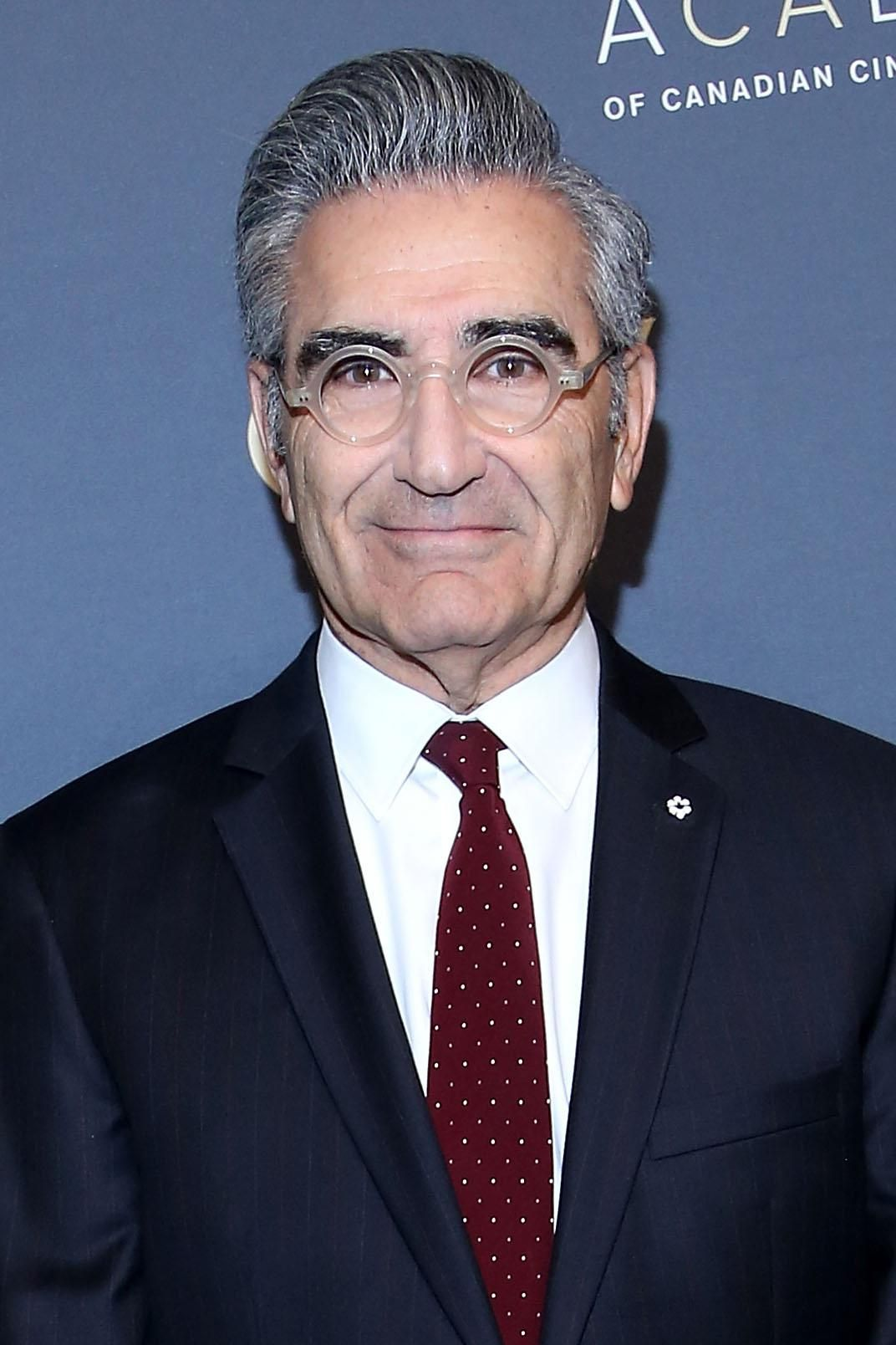 Eugene Levy in a suit and clear glasses