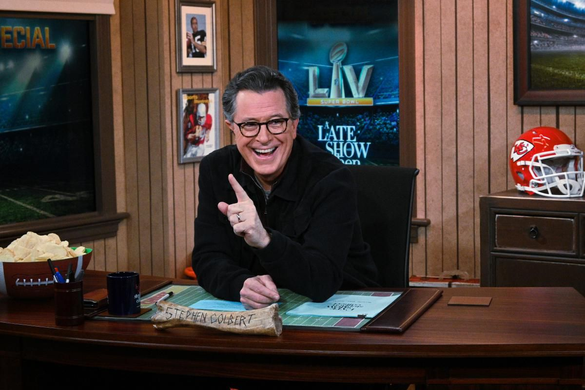 Stephen Colbert sitting at his desk and smiling