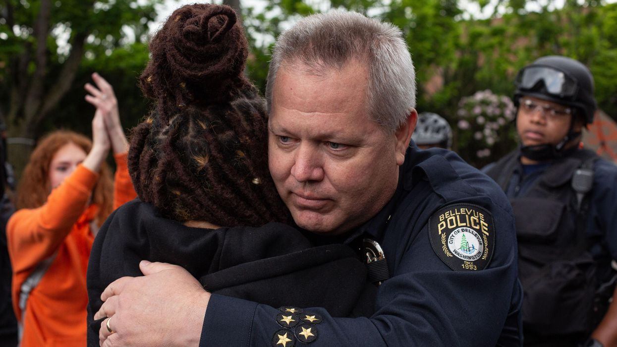 Police officer and Black Lives Matter protestor hug at a demonstration.