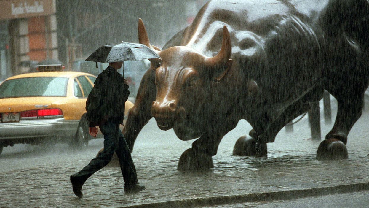 A man walks in the rain past the bull statue in Wall Street in New York City.