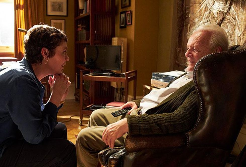 """Olivia Colman and Anthony Hopkins are pictured in a still from a movie called """"The Father."""" Colman (left) has short brown hair, and she's wearing a simple, moderately sized set of gold earrings. She wears a blue blouse. She's facing Hopkins, who plays her father, who is sitting on the right in a brown armchair. He wears a green cardigan with a white button up shirt and khakis while clutching a TV remote."""