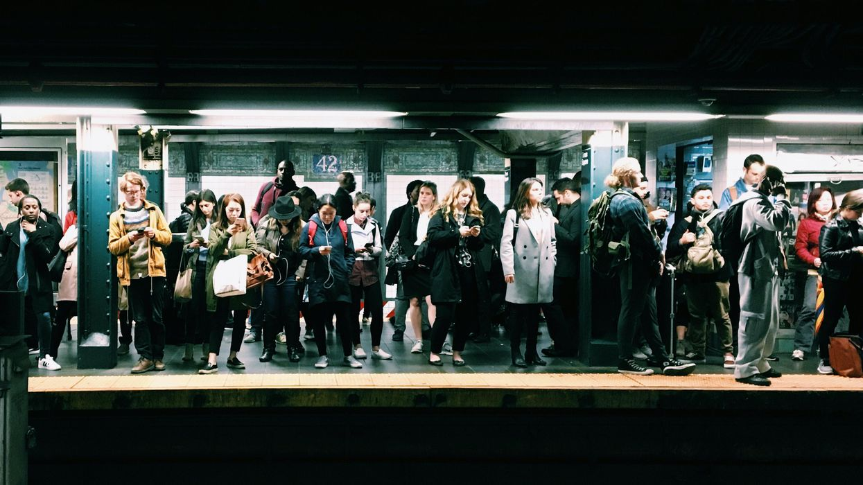 A group of people wait on crowded subway platform.