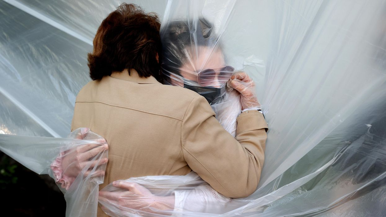 A woman hugs her relative through a plastic screen to prevent the spread of COVID-19.
