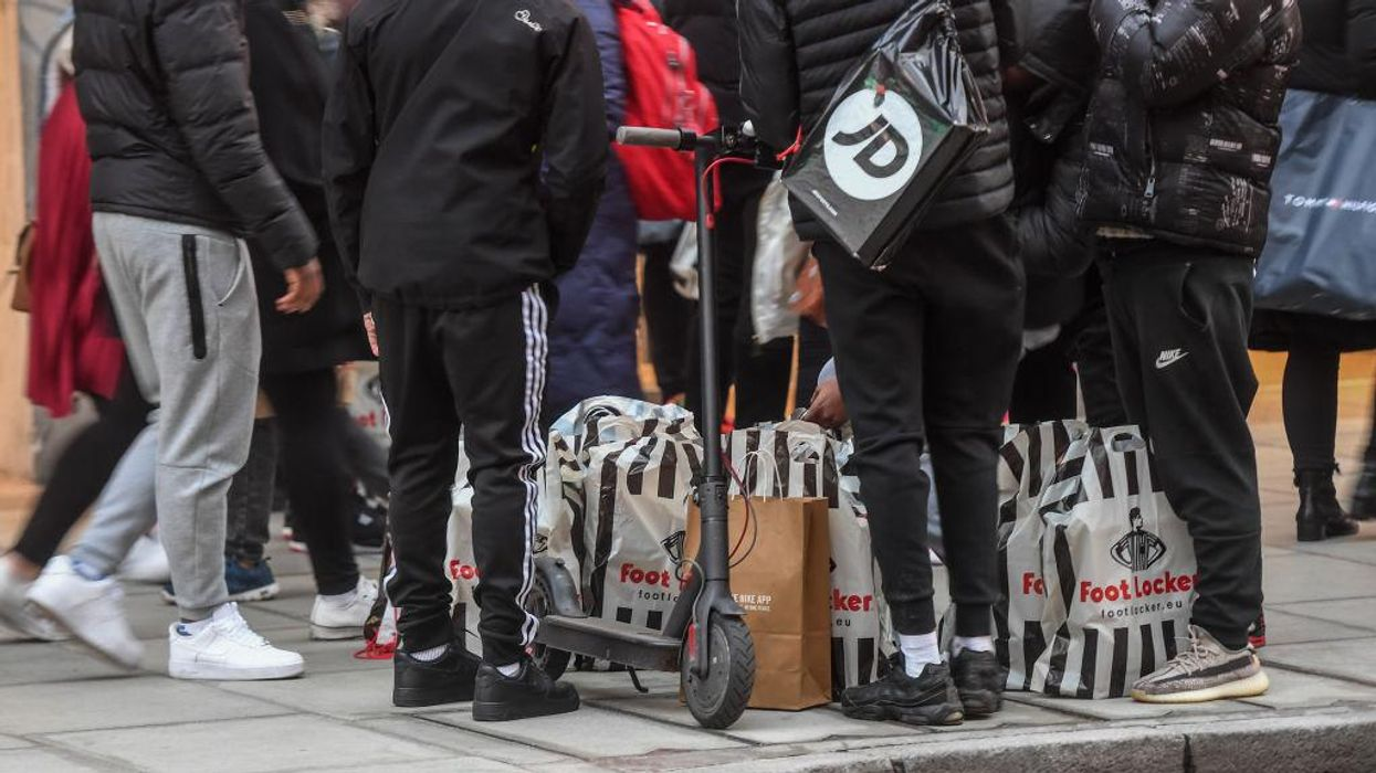 A group of men with multiple Footlocker bags in London